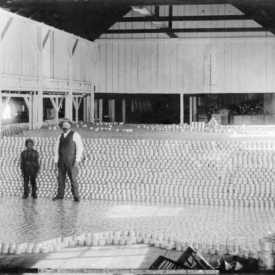 Men in front of cans, Steveston cannery