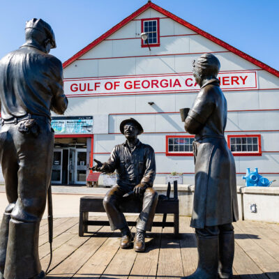 Three statues depicting cannery workers in front of the historic Gulf of Georgia Cannery