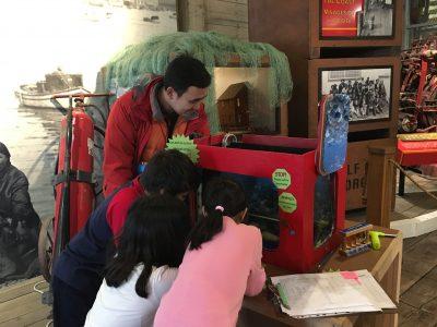 children looking into salmonid tank