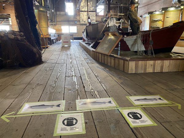 Signs on floor of cannery museum indicating stay two metres apart