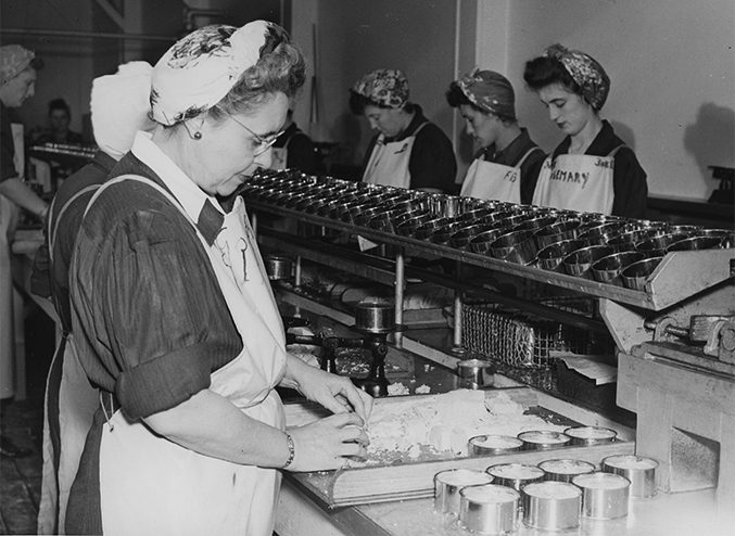 Historic photo of women working along a canning line